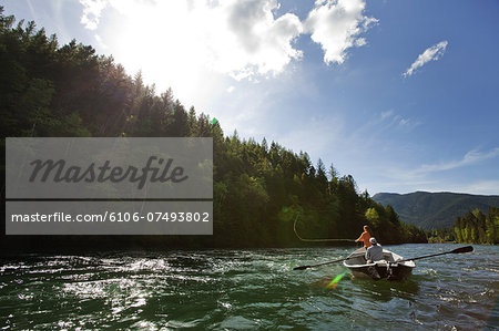 Woman fly fishing from drift boat on river. Stock Photo - Premium Royalty-Free, Image code: 6106-07493802