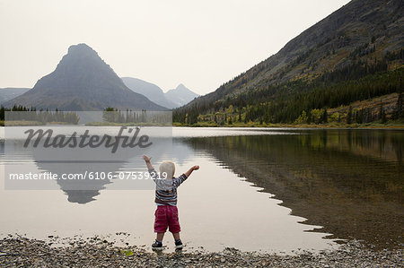 Toddler stands in mountain lake with arms raised Stock Photo - Premium Royalty-Free, Image code: 6106-07539219