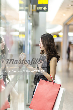 young woman looking through a shop window Stock Photo - Premium Royalty-Free, Image code: 6106-07539531