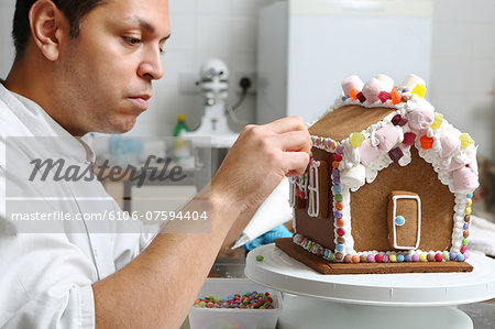 Artisan baker decorating gingerbread house Stock Photo - Premium Royalty-Free, Image code: 6106-07594404
