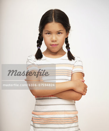 Sullen young girl in striped shirt, portrait Stock Photo - Premium Royalty-Free, Image code: 6106-07594824