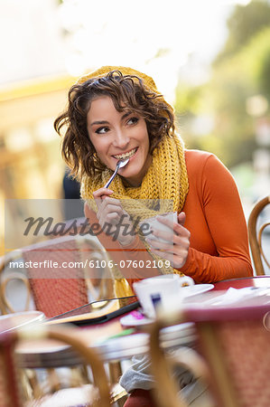 Young woman having a cafe at terrace. Stock Photo - Premium Royalty-Free, Image code: 6106-07602109