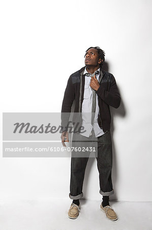 man on white adjusting tie looking up nervously Stock Photo - Premium Royalty-Free, Image code: 6106-07602431
