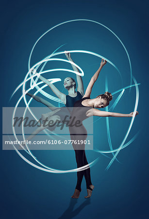 Gymnast in 3 split second motions, with light rays Stock Photo - Premium Royalty-Free, Image code: 6106-07761901