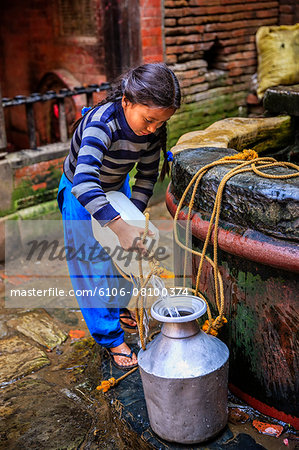 Young Nepali girl getting water from a well Stock Photo - Premium Royalty-Free, Image code: 6106-08100374