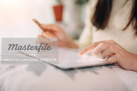 Woman doing online shopping with digital tablet Stock Photo - Premium Royalty-Free, Image code: 6106-08181416
