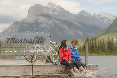 Teen couple relax on mountain dock, with bike Stock Photo - Premium Royalty-Free, Image code: 6106-08277138