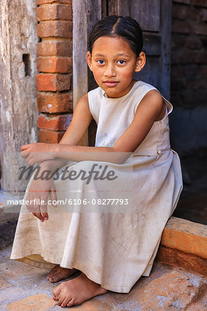 Young Nepali girl sitting outside her house Stock Photo - Premium Royalty-Free, Image code: 6106-08277793