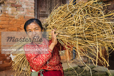 Nepali woman carrying a straw in Bhaktapur Stock Photo - Premium Royalty-Free, Image code: 6106-08277806