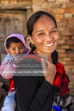 Young Nepali woman carrying her baby Stock Photo - Premium Royalty-Free, Image code: 6106-08277848