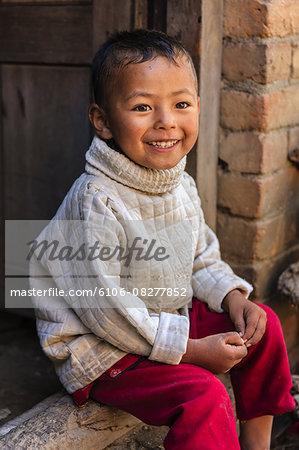 Little boy sitting next to his house Stock Photo - Premium Royalty-Free, Image code: 6106-08277852