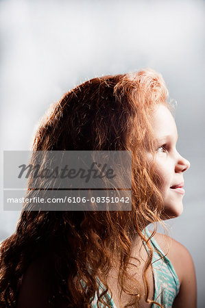 Portrait of young girl with curly red hair. Stock Photo - Premium Royalty-Free, Image code: 6106-08351042