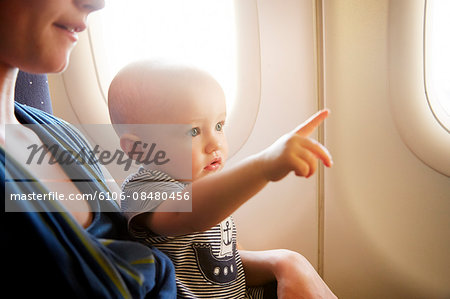 Baby on airplane pointing Stock Photo - Premium Royalty-Free, Image code: 6106-08480456