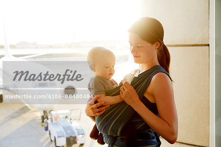 Mom with baby at airport Stock Photo - Premium Royalty-Free, Image code: 6106-08480484