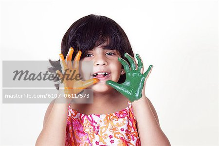 Portrait of a young girl with colored palms Stock Photo - Premium Royalty-Free, Image code: 6107-06117573