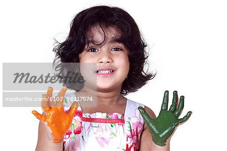 Portrait of a young girl with colored palms Stock Photo - Premium Royalty-Free, Image code: 6107-06117574