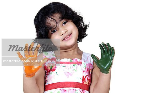 Portrait of a young girl with colored palms Stock Photo - Premium Royalty-Free, Image code: 6107-06117575