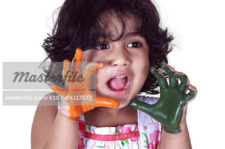 Close-up of a young girl with colored palms Stock Photo - Premium Royalty-Free, Image code: 6107-06117577