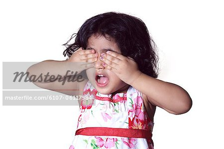 Portrait of a young girl covering her eyes with her hands Stock Photo - Premium Royalty-Free, Image code: 6107-06117584