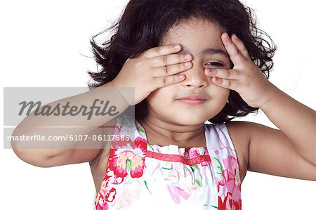 Portrait of a young girl covering her eyes with her hands Stock Photo - Premium Royalty-Free, Image code: 6107-06117585