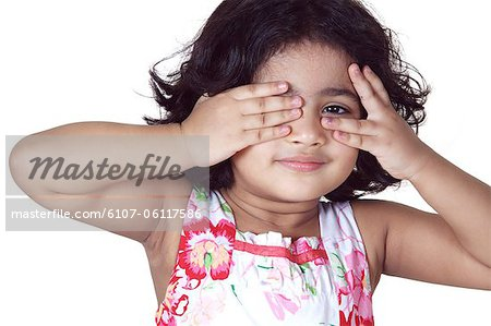 Portrait of a young girl covering her eyes with her hands Stock Photo - Premium Royalty-Free, Image code: 6107-06117586