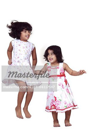 Portrait of young girls jumping Stock Photo - Premium Royalty-Free, Image code: 6107-06117587