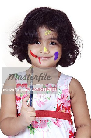 Portrait of a girl with paint brush Stock Photo - Premium Royalty-Free, Image code: 6107-06117588
