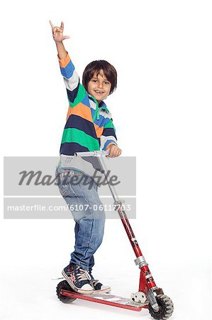 Portrait of little boy with foot push skate cycle Stock Photo - Premium Royalty-Free, Image code: 6107-06117703