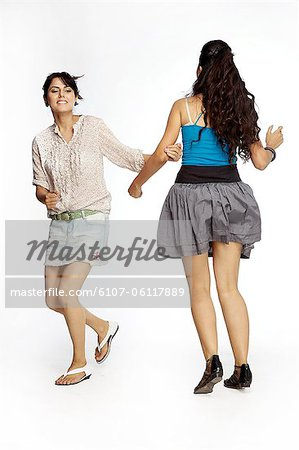 young women playing holding hands Stock Photo - Premium Royalty-Free, Image code: 6107-06117889