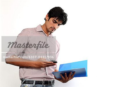 Portrait of man holding file and texting on mobile Stock Photo - Premium Royalty-Free, Image code: 6107-06117936