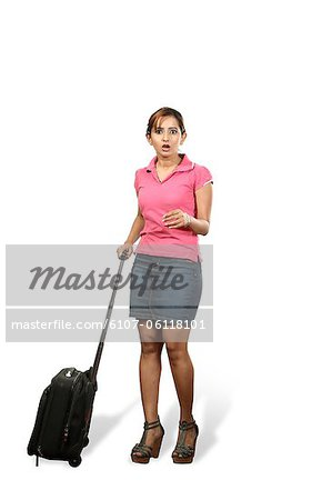 Portrait of young woman with rolling suitcase Stock Photo - Premium Royalty-Free, Image code: 6107-06118101