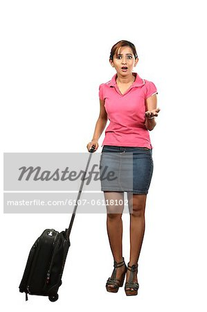 Portrait of young woman with rolling suitcase Stock Photo - Premium Royalty-Free, Image code: 6107-06118102