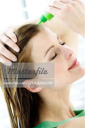 Portrait of a young woman pouring on hair lotion on her head Stock Photo - Premium Royalty-Free, Image code: 6108-05855787
