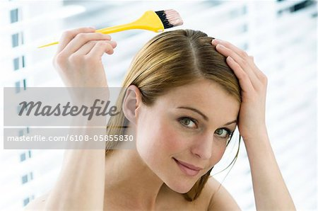 Portrait of a young woman dyeing her hair, little brush in her hand Stock Photo - Premium Royalty-Free, Image code: 6108-05855830