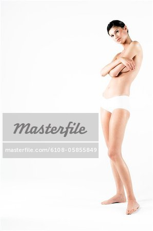 Naked woman in panties, hands on her breasts (studio) Stock Photo - Premium Royalty-Free, Image code: 6108-05855849