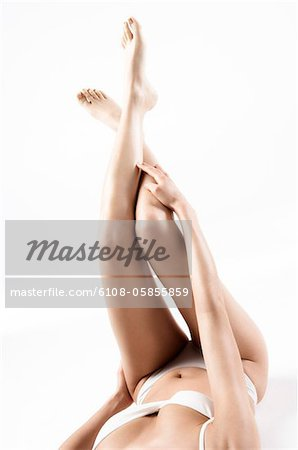 Woman in lingerie lying on floor, legs in the air, close up (studio) Stock Photo - Premium Royalty-Free, Image code: 6108-05855859