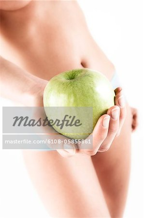 Naked woman in panties, holding a green apple, close up (studio) Stock Photo - Premium Royalty-Free, Image code: 6108-05855861