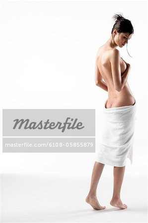 Naked woman view from the back, bath towel on her buttocks (studio) Stock Photo - Premium Royalty-Free, Image code: 6108-05855879