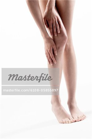 Woman legs, hands on thigh and knee, close up (studio) Stock Photo - Premium Royalty-Free, Image code: 6108-05855897