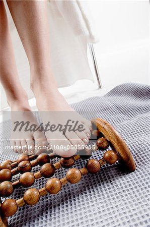 Young woman using wooden massager on her naked feet Stock Photo - Premium Royalty-Free, Image code: 6108-05855905