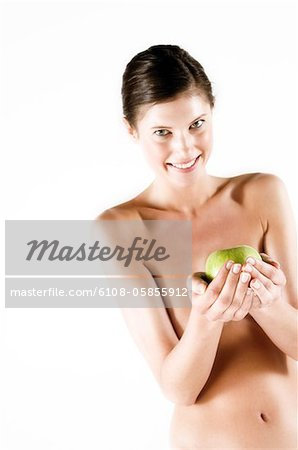 Naked woman holding a green apple, (studio) Stock Photo - Premium Royalty-Free, Image code: 6108-05855912