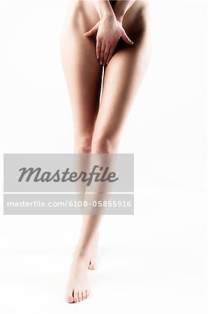 Naked woman, hands in front of her sex, legs, close up (studio) Stock Photo - Premium Royalty-Free, Image code: 6108-05855916