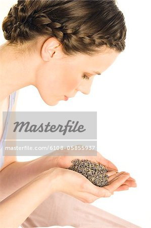 Portrait of a young woman holding grains of lavander Stock Photo - Premium Royalty-Free, Image code: 6108-05855937