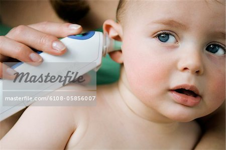 Mother taking her baby's temperature with an ear-thermometer Stock Photo - Premium Royalty-Free, Image code: 6108-05856007