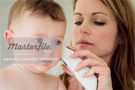 Mother taking her baby's temperature with an ear-thermometer Stock Photo - Premium Royalty-Free, Image code: 6108-05856008