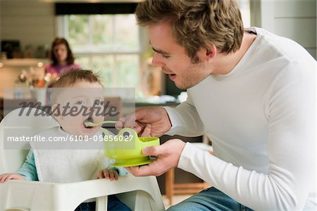 Father feeding her baby Stock Photo - Premium Royalty-Free, Image code: 6108-05856027