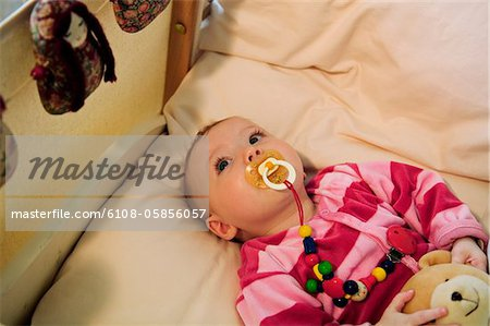 Baby in bed with comforter Stock Photo - Premium Royalty-Free, Image code: 6108-05856057