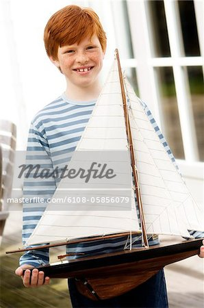 Boy holding a model boat Stock Photo - Premium Royalty-Free, Image code: 6108-05856079