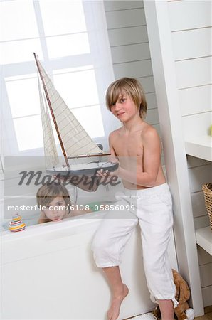 2 boys in bathroom, one having a bath, the other holding a model boat Stock Photo - Premium Royalty-Free, Image code: 6108-05856099