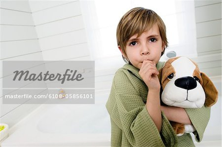 Little boy sucking his thumb, holding stuffed dog Stock Photo - Premium Royalty-Free, Image code: 6108-05856101